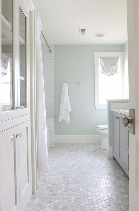 a subtle neutral bathroom with aqua walls and marble hex tiles on the floor plus blue and white bathroom furniture