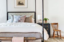 a summer bedroom with a canopy bed with bright pillows and upholstery, a dark nightstand, a wooden bench and chair and a printed rug