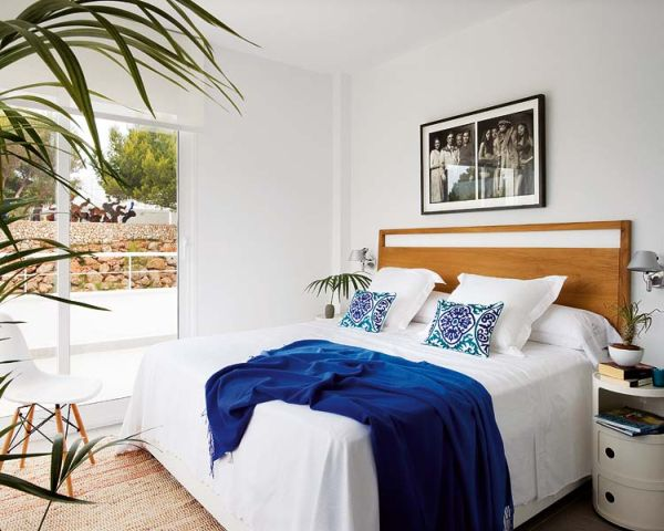 a summer bedroom with a wooden bed, neutral nightstands, an artwork and an entrance to the balcony