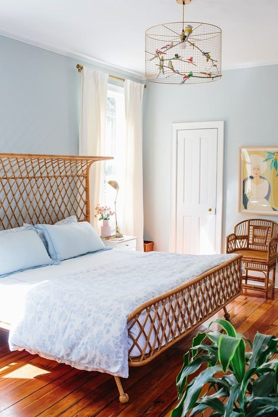 a summer bedroom with light blue walls, a rattan bed and a chair, blue bedding, a creative faux bird cage and a potted plant