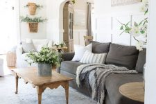 a summer cottage living room with a graphite grey sofa, white chairs, printed pillows, potted plants, layered rugs and a wooden coffee table