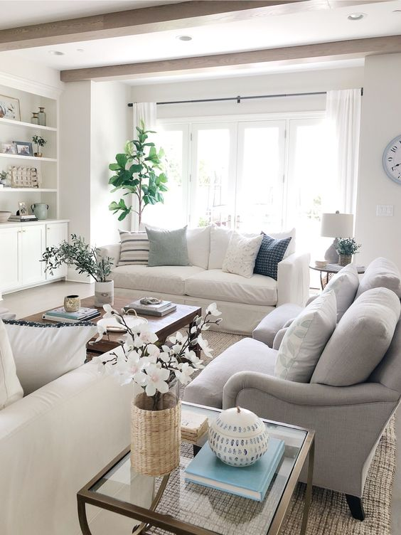 a summer living room in neutrals, with creamy and grey furniture, potted plants, a glass coffee table and some lamps