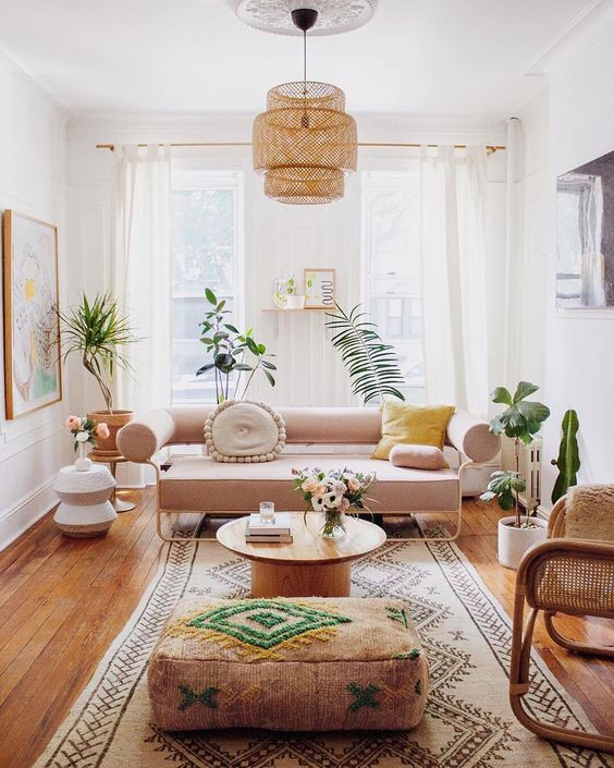 a summer living room with a blush sofa, a rattan chair, bold textiles, a woven lamp and potted plants