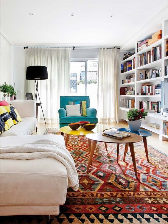 a summer living room with a creamy sectional, an arrangement of coffee tables, a turquoise chair and a boho rug