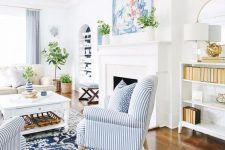 a summer living room with a fireplace, a creamy sofa, a low table, striped chairs, some potted plants and a watercolor artwork