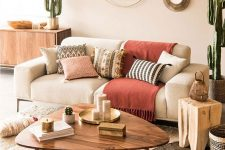 a summer living room with a neutral sofa, a coffee table, printed pillows, potted cacti and a duo of mirrors is warm
