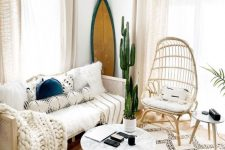 a summer living room with a surf board, creamy furniture, a coffee table, printed pillows and a rug plus a potted plant