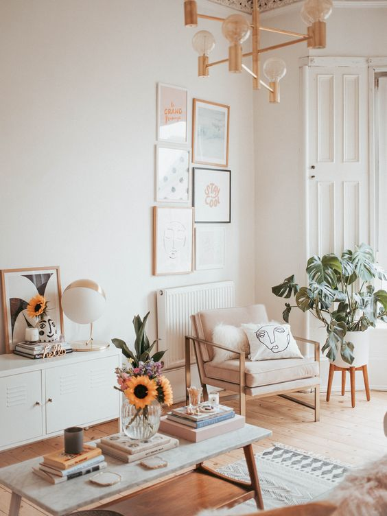 a summery living room in neutrals, with neutral furniture, potted plants, a chandelier and a low coffee table plus some printed pieces