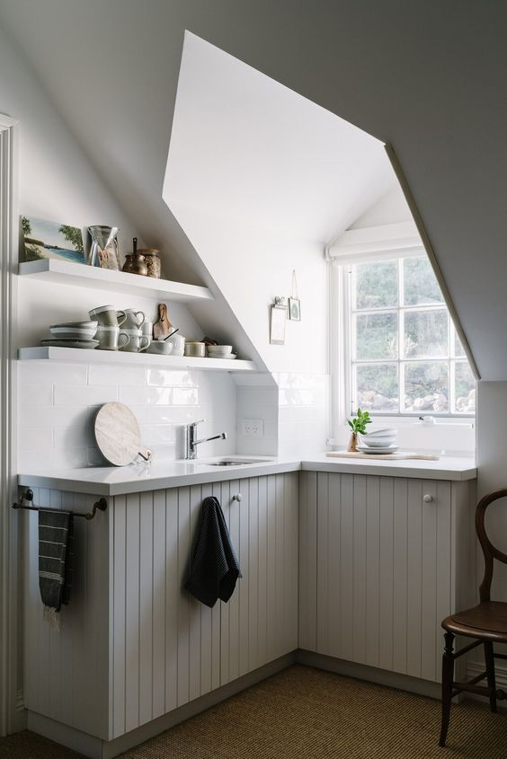 a tiny attic kitchen with a window, planked cabinets, open shelves and a vintage chair is a lovely idea to rock