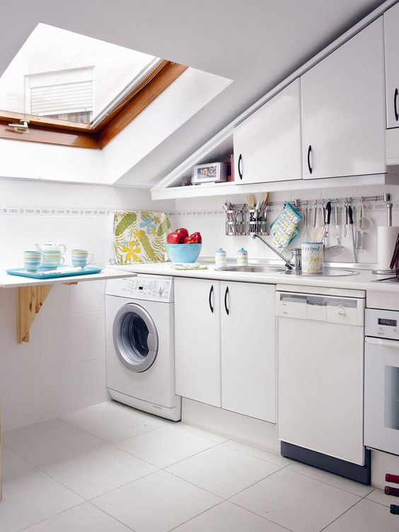 a tiny attic kitchen with sleek cabinetry, a small folding table, colorful tableware and a skylight