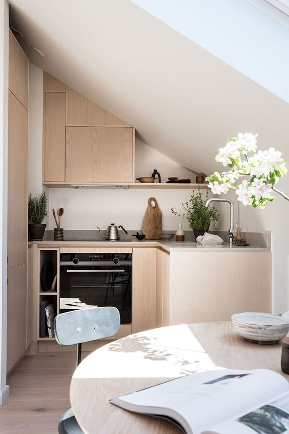 a tiny minimalist kitchen with sleek plywood cabinets, built-in appliances, a round table and grey chairs