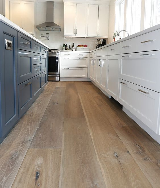 a two-tone kitchen in blue and white, with laminate flooring, white walls and windows for natural light
