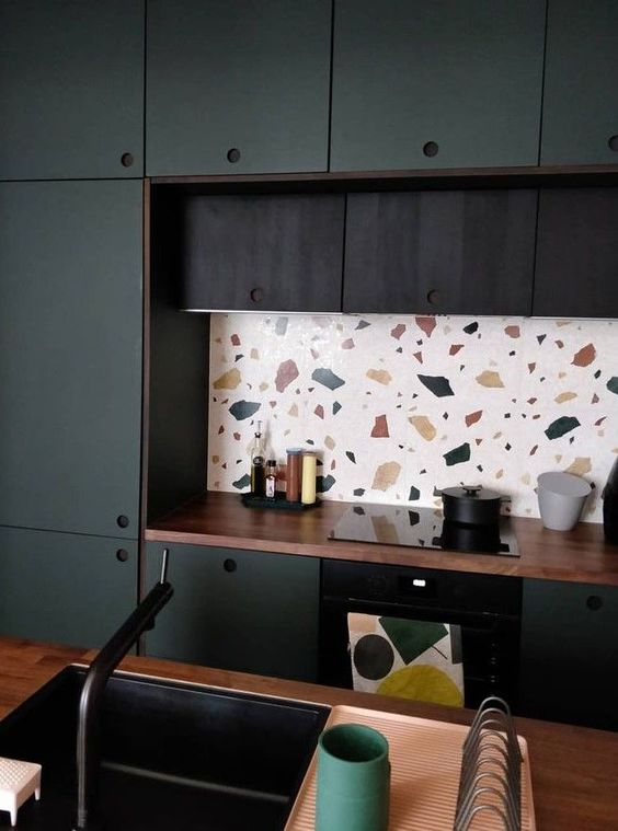 a two-tone kitchen in dark green and black, with butcherblock countertops and a cheerful bright terrazzo backsplash