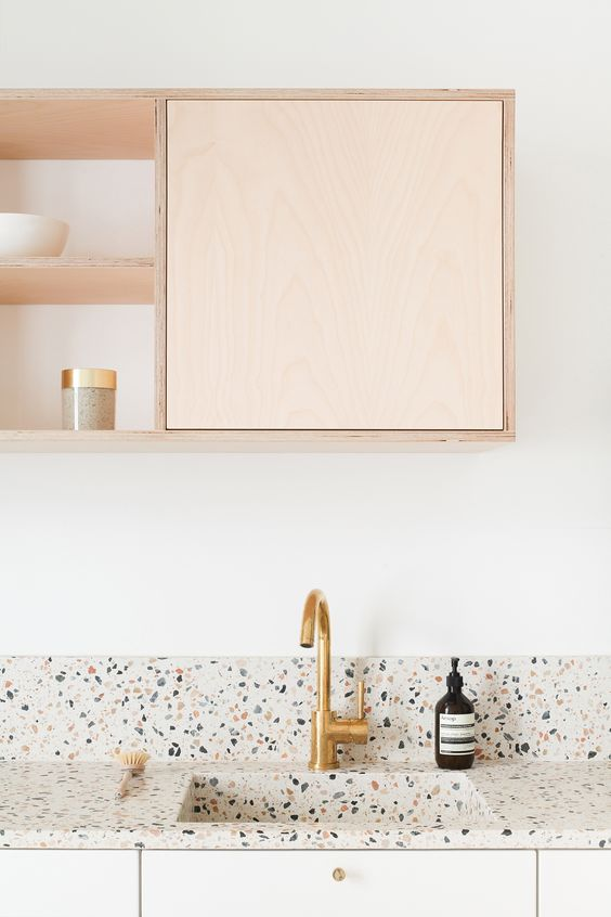 a two-tone kitchen with a pretty and bright terrazzo backsplash and countertops that make the space more interesting