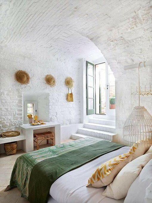 a unique white summer bedroom with neutral and rattan furniture, yellow and green bedding, hats for decor and some baskets