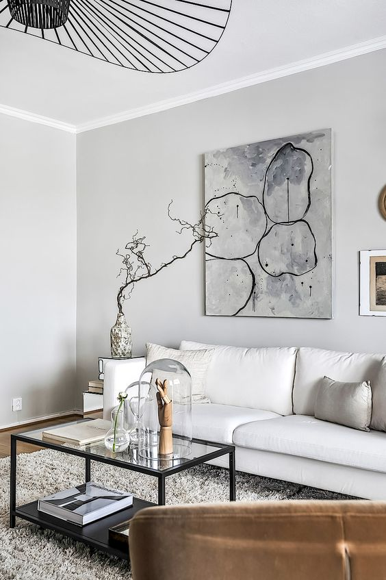 a very elegant modern living room with a white sofa, a stylish tiered coffee table, a statement artwork and a black chandelier