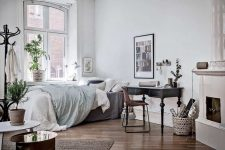 a vintage Scandinavian bedroom with a stove, a bed with pastel bedding, a dark desk with a leather chair and potted plants