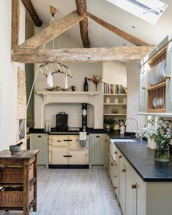 a vintage attic kitchen with grey cabinetry, a stove, wooden beams, a wooden console table and some open storage units