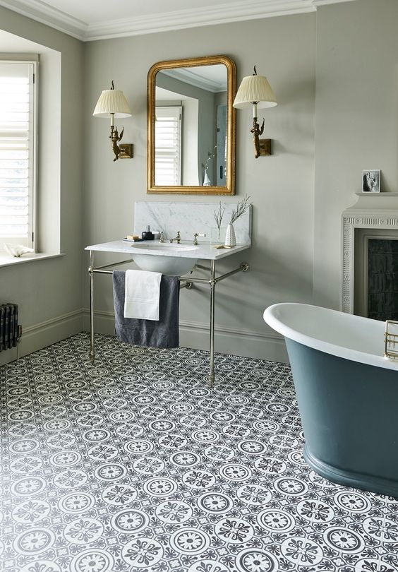 a vintage bathroom with grey green walls, a printed vinyl floor, a non-working fireplace, a grey bathtub and a sink on a stand