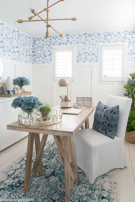 a vintage coastal home office with white paneling, blue wallpaper, a trestle desk, a white chair and blue textiles is chic