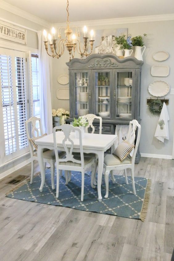 a vintage dining room with grey walls and a grey vinyl floor, a vintage white dining set, a grey buffet, lots of greenery and blooms in jugs