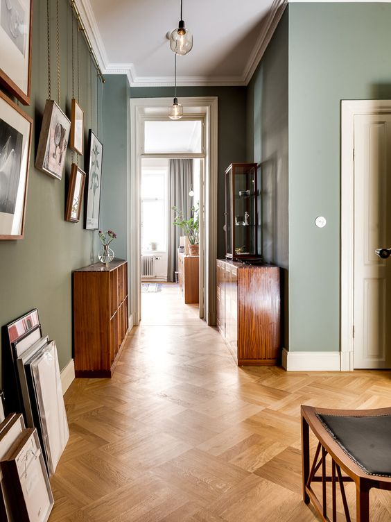 a vintage-isnpired space with green walls, stained furniture, lots of artworks and pendant lamps is amazing