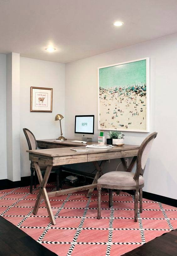 a vintage shared coastal home office with a pink printed rug, a shared wooden desk, a large beach artwork and brass touches