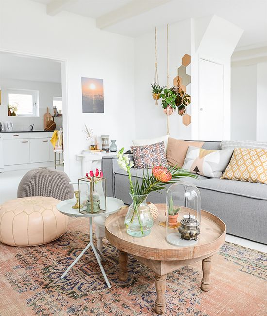 a vivacious living room with a grey sofa, a round table, lovely poufs, colorful pillows and potted plants is amazing