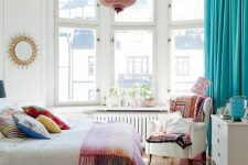 a vivacious summer bedroom with a bow window, neutral furniture, colorful printed textiles, a pink pendant lamp and turquoise curtains