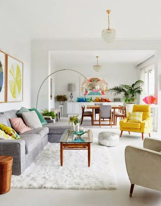 a vivacious summer living room with a grey sectional, a low coffee table, an ivory and yellow chair, a floor lamp
