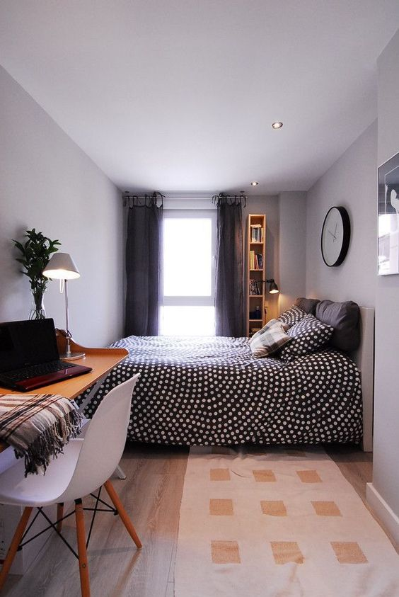 a welcoming bedroom with grey walls and a ceiling, anupholstered bed with pretty bedding, a floating desk and a white chair for work