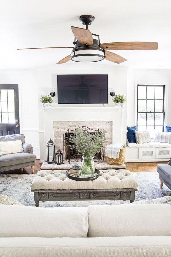 a welcoming living room in neutrals, with a fireplace and comfy furniture, a windowsill daybed and potted plants
