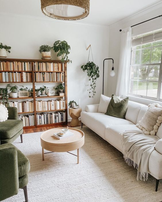 a welcoming living room with a large bookshelf, a white sofa, green chairs, a round table, potted plants and lamps all over
