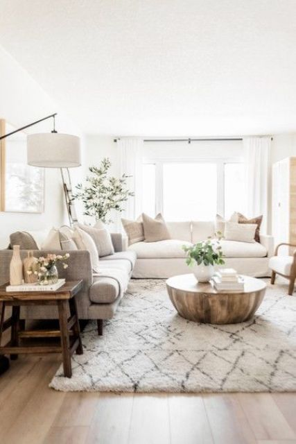 a welcoming modern farmhouse living room wiht a white and agrey sofa, a round metal table, a wooden stool, a floor lamp and some greenery