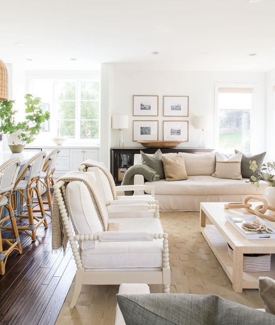 a welcoming modern farmhouse living room with a white sofa, white chairs, a low coffee table, printed pillows and a gallery wall