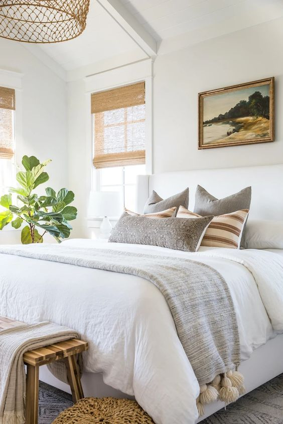 a welcoming neutral bedroom with a white bed, a wooden bench, a woven pendant lamp and shades on the windows