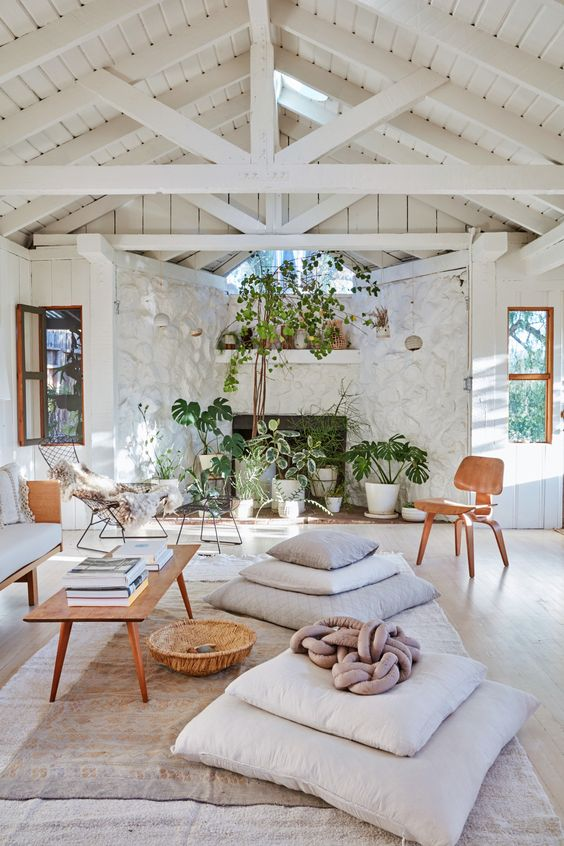 a welcoming summer living room with a stone wall and an attic ceiling, neutral furniture and pillows, a low coffee table and potted plants
