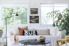 a welcoming summer living room with a white sofa, a black coffee table, printed pillows, black and white artworks and a potted plant