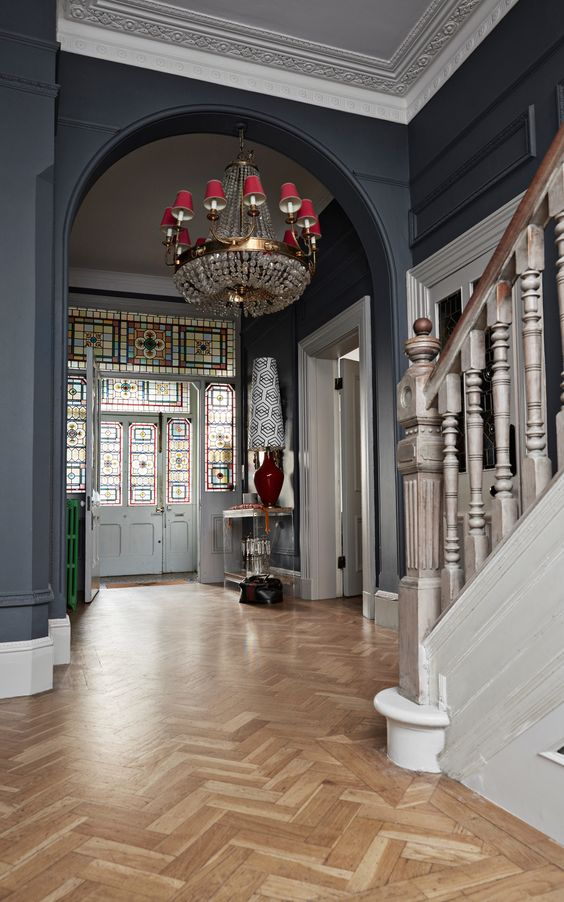 a whimsical entryway with black walls and a parquet floor, a mosaic door and a catchy chandelier plus touches of color