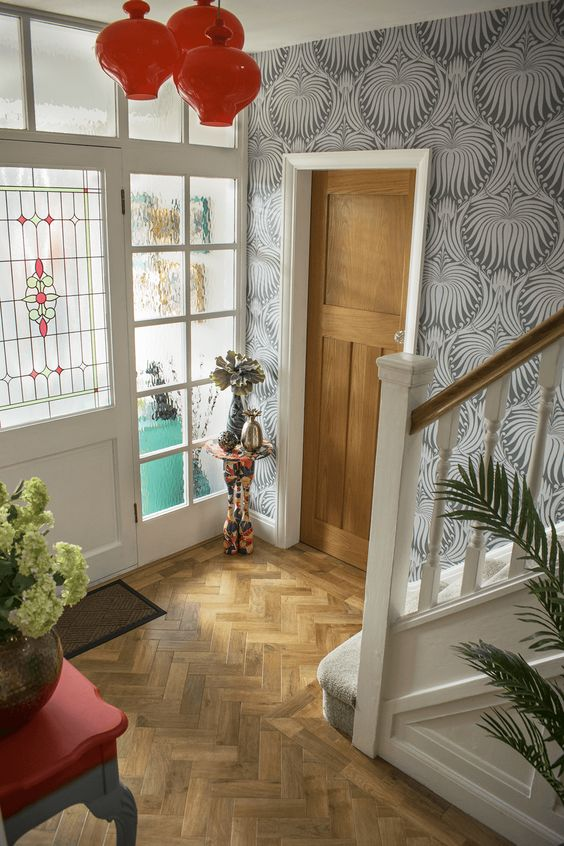 a whimsical entryway with wallpaper walls, light stained parquet, a red console table and a quirky side one plus red pendant lamps