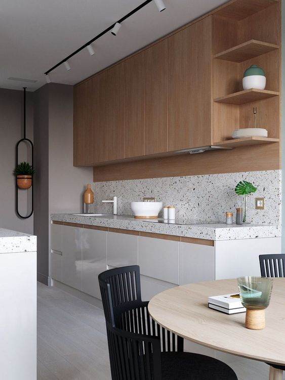 a white and stained kitchen is made catchier with a white terrazzo backsplash and countertops and the same countertops on the kitchen island