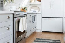 a white farmhouse attic kitchen with shaker style cabinets and planked walls, potted plants and a striped rug