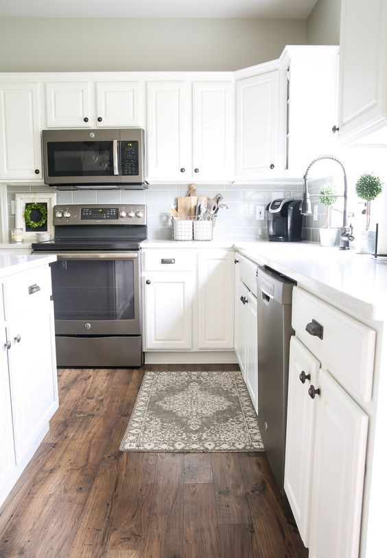 a white farmhouse kitchen with a dark laminate floor that contrast each other and make the space look amazing
