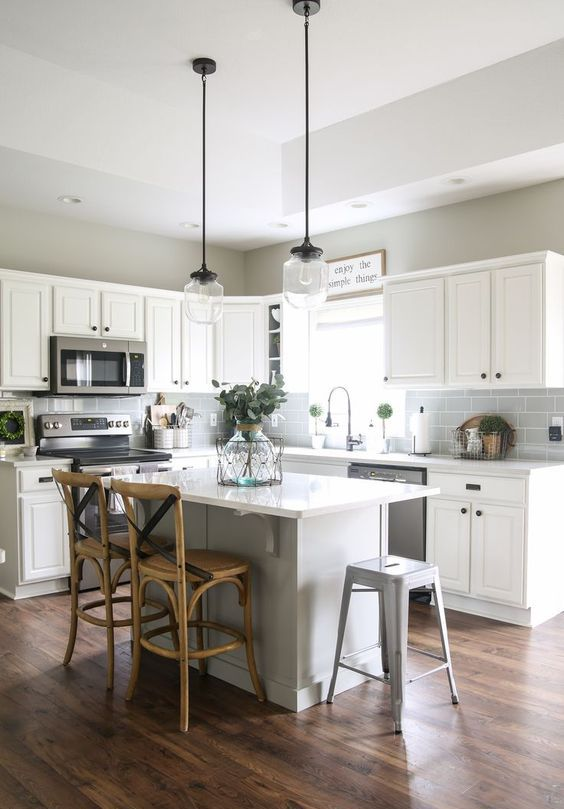 a white farmhouse kitchen with dark laminate floors, a grey subway tiles, pendant lamps and rattan stools is chic and cool