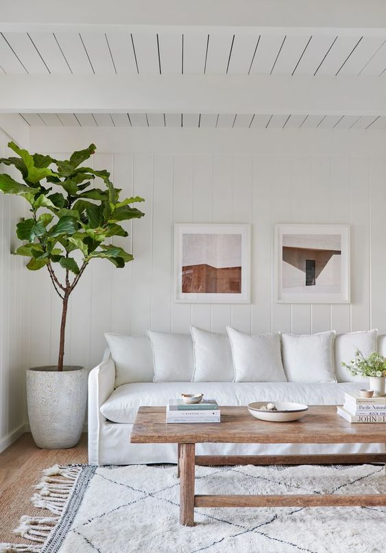 a white farmhouse living room with a white sofa, a printed rug, a wooden coffee table, a potted plant and a gallery wall
