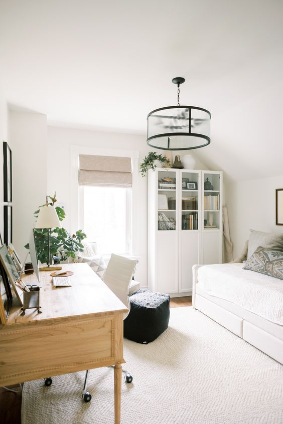 a white guest bedroom with a daybed, a large desk with a white leather chair, potted plants and a small ottoman is chic