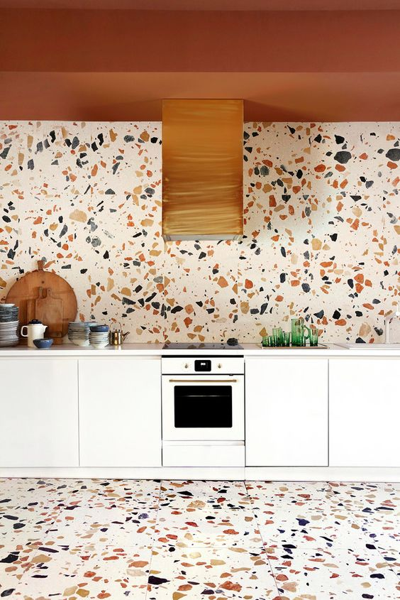 a white kitchen made eye-catchy with a terracotta-colored ceiling, a bright terrazzo backsplash and a matching floor
