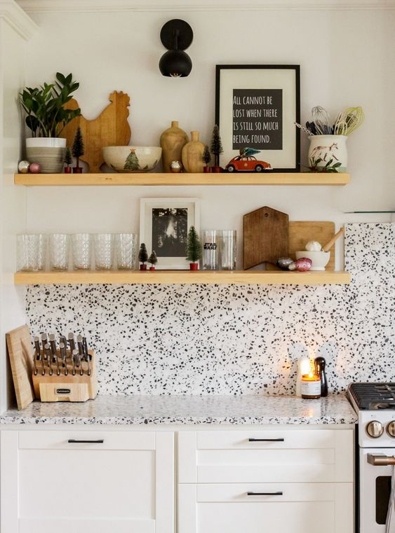 a white shaker style kitchen with black handles and a white terrazzo backsplash and countertops plus floating shelves