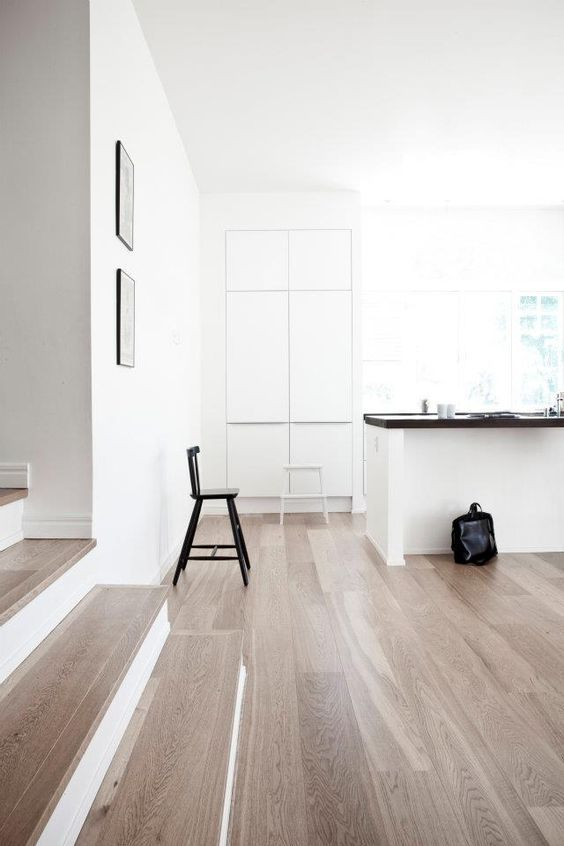 an airy Nordic space with white walls, lots of natural light, light-colored laminate flooring, black and white furniture is chic