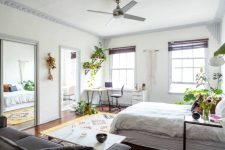 an airy and neutral bedroom with a large bed, a grey sofa, a low table, a cozy working corner and lots of potted plants